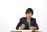 机に座る男子高校生