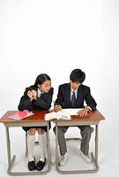 机に座る高校生二人