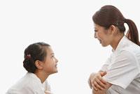 女の子と向い合う歯科助手