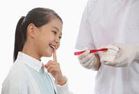 女の子とブラッシング指導をする歯科医師
