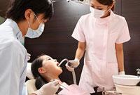 女の子の口腔内を洗浄する歯科助手