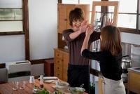 キッチンでハイタッチをする若いカップル