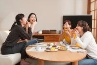 菓子を頬張る四人の女性