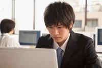パソコンを真剣に見るスーツ姿の若い男性