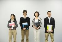 ファイルとノートを持ち並んで立つ男女4人