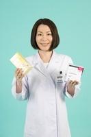 薬のパッケージを持つ女性薬剤師