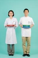薬のボードを持つ薬剤師と登録販売者