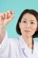 カプセルを眺める女性薬剤師