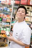 商品棚の前で薬を持つ笑顔の男性登録販売者