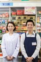 商品棚の前に立つ薬剤師とアルバイト店員