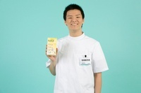 薬のパッケージを持つ笑顔の男性登録販売者