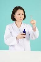 メートグラスとガラス瓶を持つ女性薬剤師