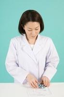 処方箋と薬を確認する女性薬剤師