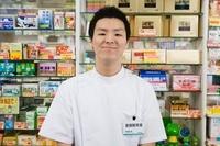 薬の商品棚の前に立つ男性登録販売者