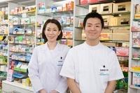 薬の商品棚の前に立つ薬剤師と登録販売者