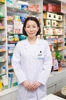 薬の商品棚の前に立つ女性薬剤師