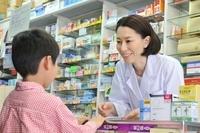 カウンターで子供と話す女性薬剤師