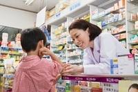 子供の腕の状態を確認する女性薬剤師