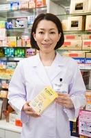 商品棚の前で薬を持つ笑顔の女性薬剤師
