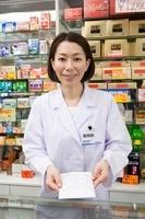 薬袋を持つ笑顔の女性薬剤師