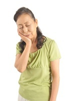 歯の痛みを感じて頬に手を当てるシニア女性