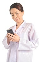 スマートフォンを操作する白衣の女性