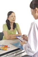 シニア女性の問診をする白衣の女性 11002059838| 写真素材・ストックフォト・画像・イラスト素材|アマナイメージズ