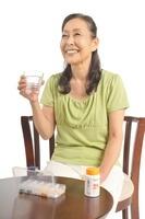 錠剤を水で飲もうとするシニア女性