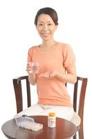 錠剤を水で飲もうとする女性