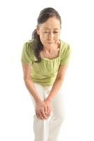 膝を抱えて前かがみになるシニア女性