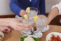 お酒の入ったグラスで乾杯する男性の手元