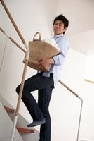 洗濯籠を持って階段を上がる男性