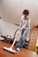 床に掃除機をかける男性