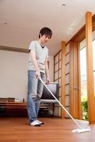 フローリングワイパーで掃除をする男性