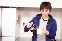 コーヒーをマグカップに注ぐ男性