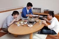 鍋を囲んで食事をする男性3人