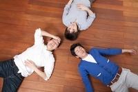 輪になって床に寝そべる男性3人