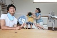 男の子に保冷剤を巻く母親と団扇を持つ父親