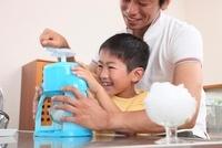 かき氷を作を作って喜ぶ男の子と父親