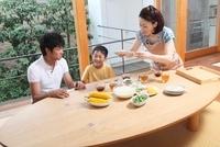 食卓に料理を並べる母親と家族
