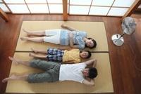 扇風機をつけながら並んで昼寝をする家族