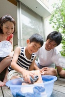 洗濯板で洗う男の子と両親