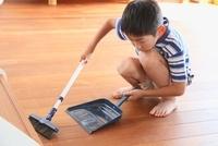 箒とちりとりで部屋の掃除をする男の子