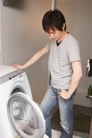 洗濯機のフタをあけた男性