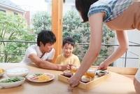料理を運ぶ母親と座って待つ父親と男の子