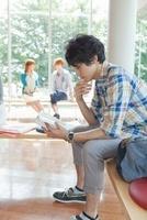 椅子に座って読書をする大学生