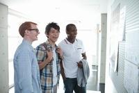 掲示板の前で笑う大学生と留学生3人