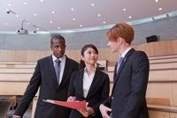 書類を見ながら話すスーツ姿の男女3人