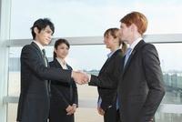 握手をするスーツ姿の男女4人