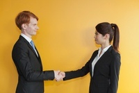 握手をするスーツ姿の若い女性と外国人男性
